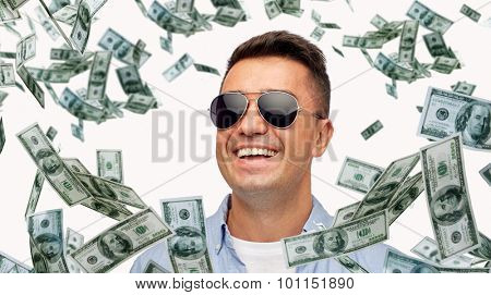 business, finance, success and people concept - face of smiling middle aged latin man in shirt and sunglasses with heap of falling dollar money