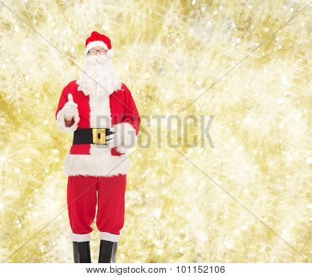 christmas, holidays, gesture and people concept- man in costume of santa claus showing thumbs up over yellow lights background
