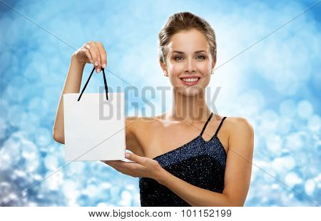 shopping, luxury, advertisement, holydays and sale concept - smiling woman with white blank shopping bag over blue lights background