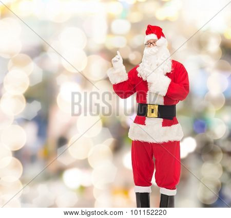 christmas, holidays, gesture and people concept - man in costume of santa claus pointing fingers over lights background