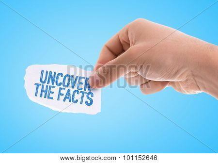 Piece of paper with the word Uncover the Facts with blue background