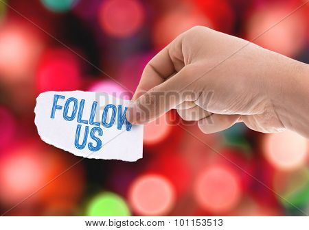 Piece of paper with the word Follow Us with bokeh background