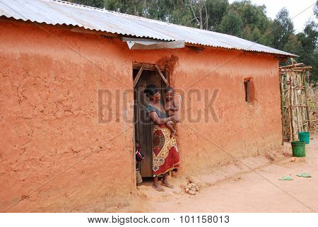 An Unidentified African Woman With Her Children On The Doorstep 36