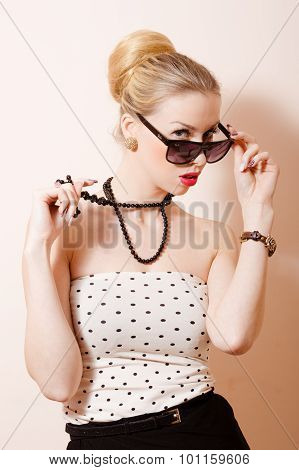 Picture of young pinup blond woman in accessoties and sunglasses