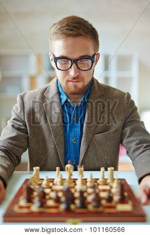 Serious businessman looking at chess on chessboard
