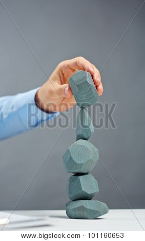 Businessman building tower from grey stones