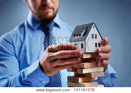 Businessman putting house model on top of tower from small wooden blocks