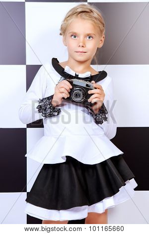 Portrait of a pretty little girl in white shirt and black skirt posing over chessboard background. Studio shot. Kid's beauty, fashion. Education.
