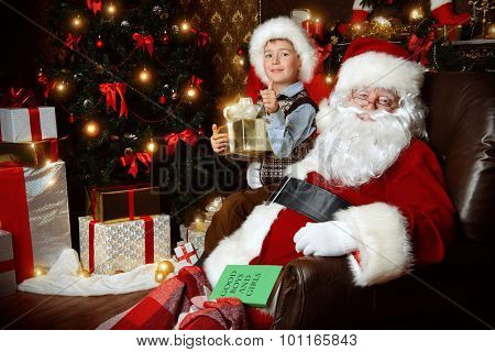 Santa Claus and laughing cute boy sitting in Christmas room with gifts. Christmas home décor.