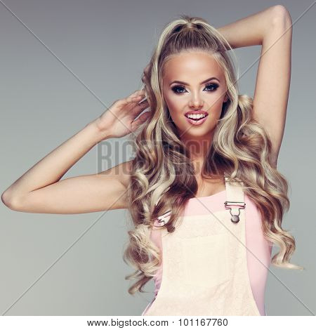 Closeup portrait of a young glamorous lady with beautiful blond hair on grey background