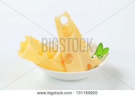pieces of fresh Swiss cheese in white bowl