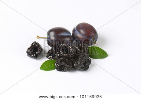 fresh and dried plums on white background
