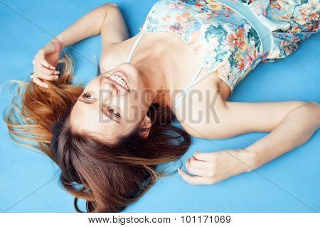 young pretty woman fooling around on blue background