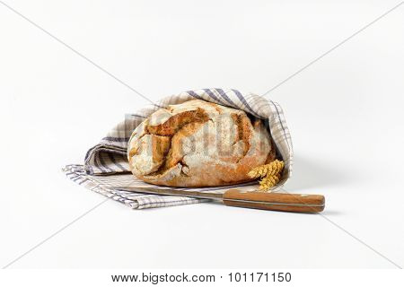 loaf of homemade bread in wrapped checkered dishtowel and kitchen knife on white background