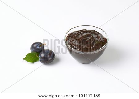 bowl of fresh plum jam and ripe plums on white background