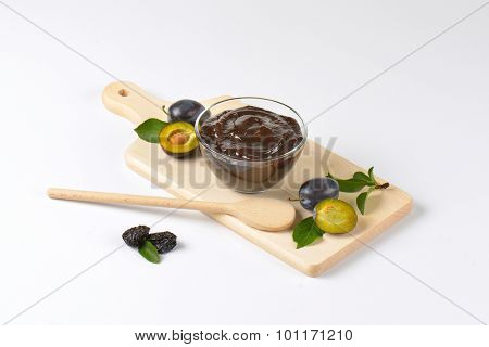 bowl of fresh plum jam, plums and wooden spoon on cutting board