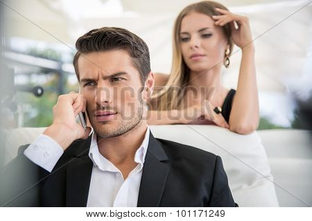 Portrait of a handsome man talking on the phone outdoors in restaurant with woman on background