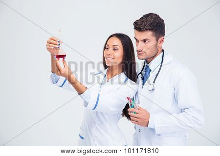 Portrait of a two medical workers looking at tube with liquid isolated on a white background