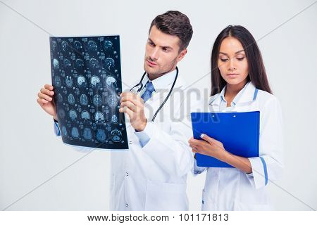 Portrait of a male doctor looking at x-ray picture of brain and woman writing diagnose isolated on a white background