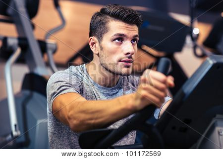 Portrait of a handsome man workout on a fitness machine at gym