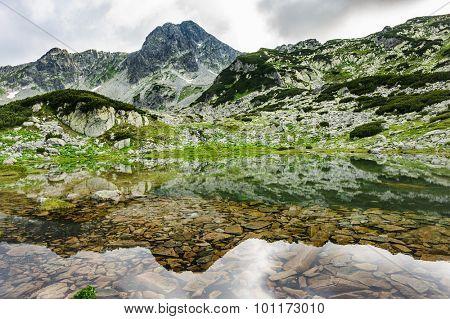 Small mountain lake in Retezat National Park, Transylvania, Romania, Europe. Stones under transparent see-through water.