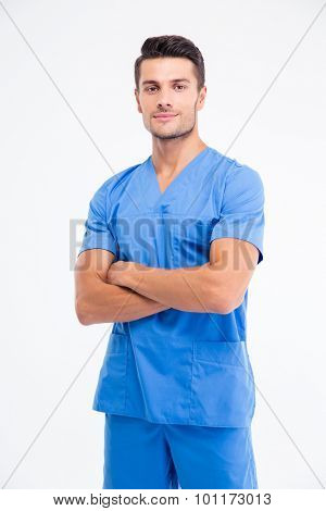 Portrait of a handsome male doctor standing with arms folded isolated on a white background. Lookign at camera