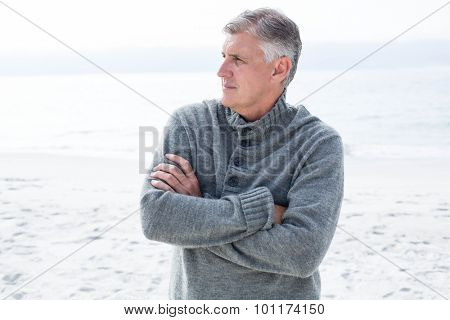 Man with crossed arms looking away at the beach