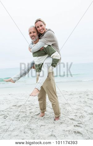 Man giving his partner a piggy back at the beach