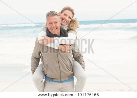 Smiling man giving woman a piggy back at the beach
