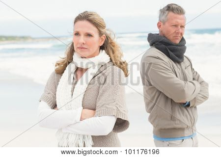 Upset couple look away from each other at the beach