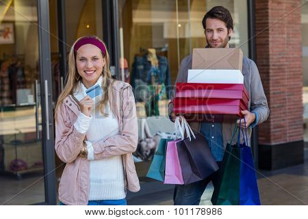 Portrait of smiling couple showing credit card and carrying boxes at shopping mall