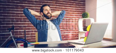 Creative businessman with hands behind back relaxing in office