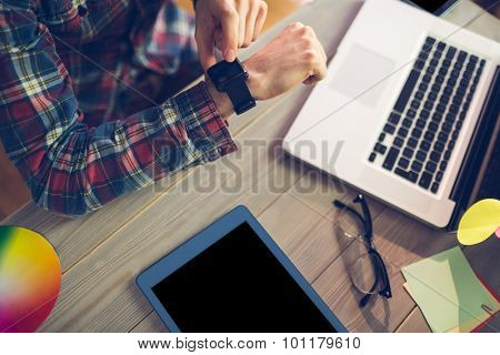 Midsection of businessman with laptop and graphic tablet checking time in office