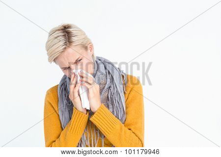 Close up of woman blowing her nose with a tissue