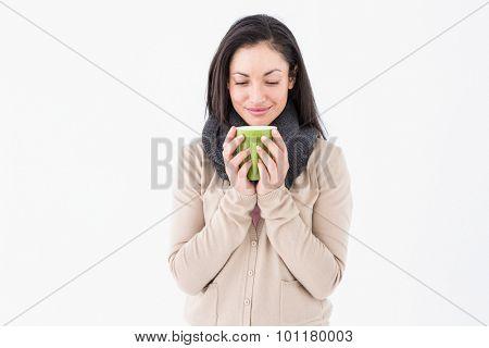 Smiling brunette smelling hot beverage on white background
