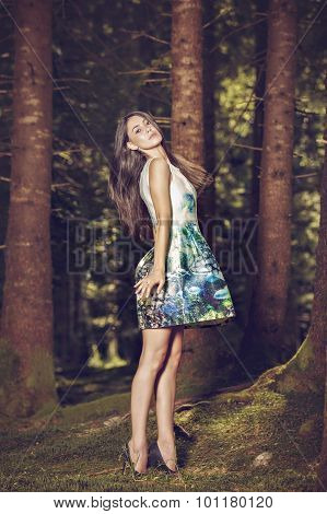Beautiful young fashion woman in color dress posing outdoor in garden