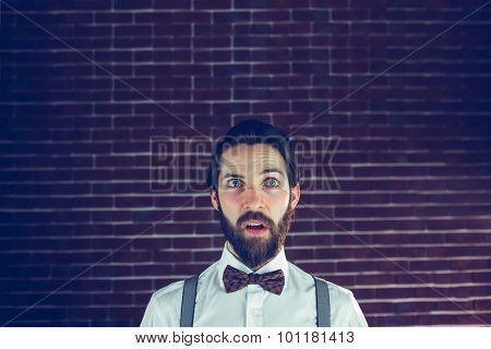 Confused handsome man looking away against brick wall