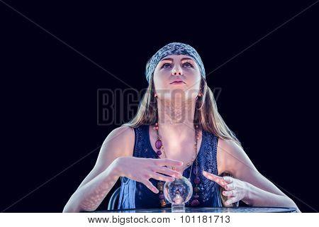 Fortune teller using crystal ball on black background