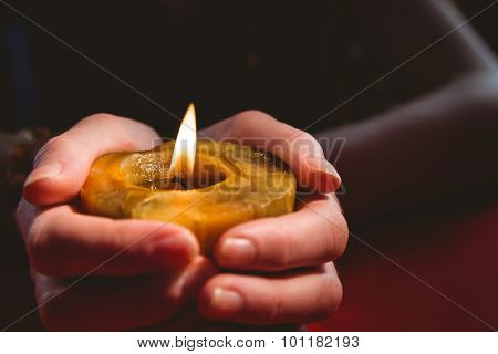 Fortune teller holding a candle on red table