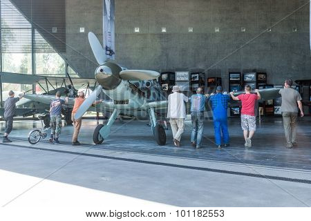 KRAKOW MUSEUM OF AVIATION, POLAND - JUL,  2015:  Exhibition plane in the aviation Museum in Krakow, Poland on July, 2, 2015. Museum workers roll the plane to the exhibition pavilion
