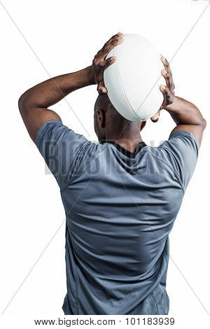 Rear view of sportsman throwing rugby ball over white background