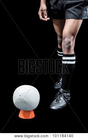 Rugby ball on kicking tee while sportsman standing against black background