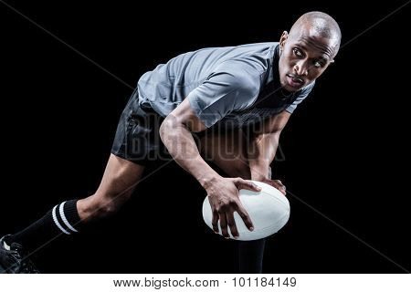 Determined sportsman looking away while playing rugby against black background