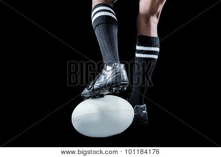 Sportsman keeping leg on ball while playing rugby against black background
