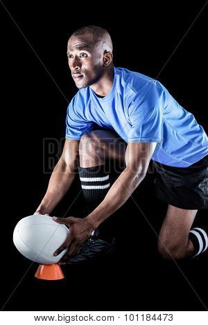 Sportsman looking away while keeping rugby ball on kicking tee over black background