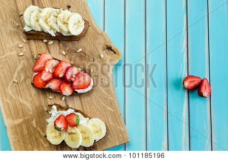 Bruschetta With Cheese Ricotta, Strawberry And Banana Over Wooden Turquoise Background
