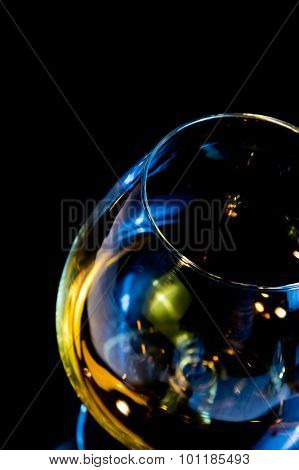Top Of View Of Snifter Of Brandy In Elegant Typical Cognac Glass On Black Background With Blue Refle