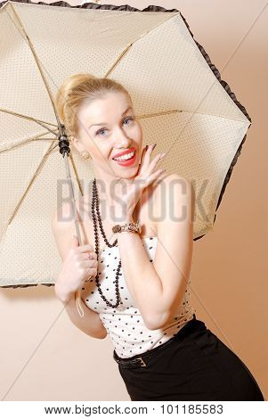 Young blonde pin-up lady under umbrella