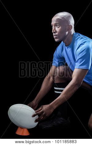 Rugby player looking away while keeping ball on kicking tee against black background