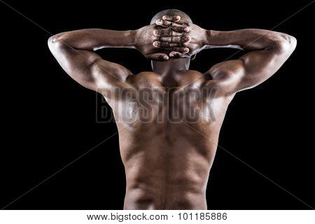 Rear view of muscular athlete stretching with hands behind head against black background